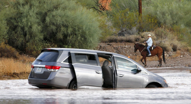 A horseback rider takes a look at a car as it rests abandoned in the floodwaters of Skunk Creek after the driver was rescued Tuesday, October 20, 2015, in Desert Hills, Ariz. Heavy rains swept through many areas of Arizona, like Desert Hills just north of the Phoenix metro area. (Photo by Ross D. Franklin/AP Photo)