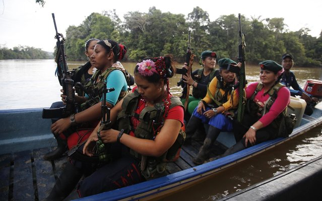 """Rebels soldiers of the 48th Front of the Revolutionary Armed Forces of Colombia, or FARC, board a boat to travel to a local intramural soccer tournament, in the southern jungles of Putumayo, Colombia, Friday, August 12, 2016. The """"FARC Olympics"""", coinciding with the Rio Games, began early in the morning as dozens of guerrillas made their way by motorized longboat through the jungle waterways to the camp of the 49th front. (Photo by Fernando Vergara/AP Photo)"""