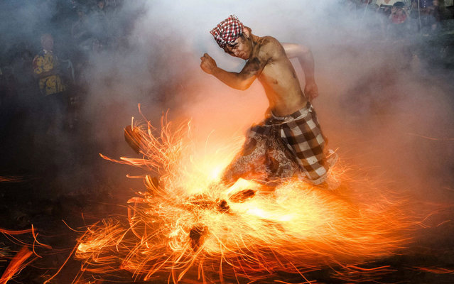 "A Balinese man kicks up fire during the ""Perang Api"" ritual ahead of Nyepi day, which falls on Tuesday in Gianyar on the Indonesian island of Bali, on March 12, 2013. Nyepi is a day of silence for self-reflection to celebrate the Balinese Hindu new year, where Hindus in Bali observe meditation and fasting, but are not allowed to work, cook, light lamps or conduct any other activities. (Photo by Reuters/Stringer)"