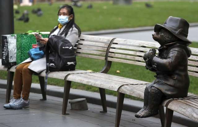 A woman rests sits with shopping next to a statue of Paddington Bear in London, Friday, October 9, 2020. The British economy grew by far less than anticipated during August, raising concerns that the recovery from the coronavirus recession was already stuttering even before the reimposition of an array of lockdown restrictions. (Photo by Frank Augstein/AP Photo)