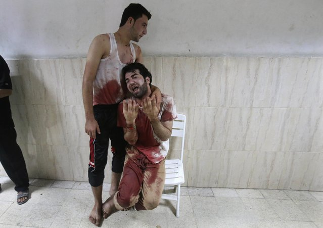 A Palestinian man in clothes stained with the blood of his father, whom medics said was killed by Israeli shelling, mourns at a hospital in Khan Younis in the southern Gaza Strip, in this July 23, 2014 file photo. (Photo by Ibraheem Abu Mustafa/Reuters)