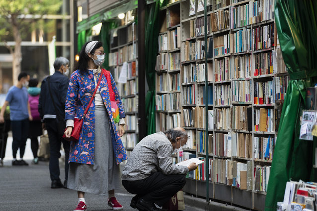 People wearing face masks shop around at a secondhand book store in Tokyo on Thursday, October 29, 2020. (Photo by Hiro Komae/AP Photo)