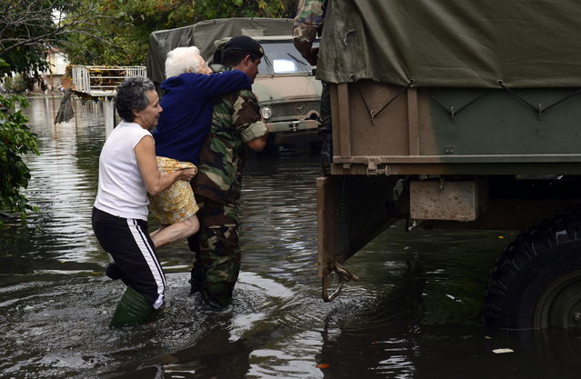 A soldier evacuates an elderly woman in a flooded street in La Plata, 63 kms southeast of Buenos Aires on April 3, 2013. At least 25 people died in flooding in the Argentine city of La Plata as torrential rains fell, according to the regional governor. The deaths raised to 33 the number of people killed this week following record heavy rain in Argentina. (Photo by Daniel Garcia/AFP Photo)