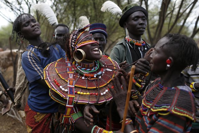 Pokot men and women hold a girl before she is taken away by a group of men to be married to a member of their community after the group came to take her from her family home, about 80 km (50 miles) from the town of Marigat in Baringo County December 7, 2014. (Photo by Siegfried Modola/Reuters)