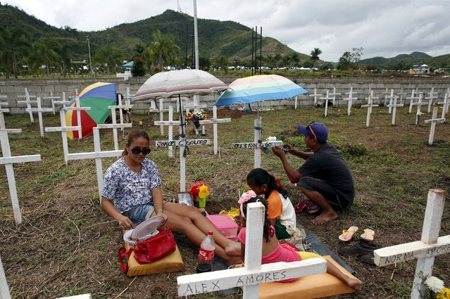 Residents visit the graves of two family members at a mass grave for Typhoon Haiyan victims on All Saints Day in Tacloban city in central Philippines November 1, 2015. (Photo by Erik De Castro/Reuters)
