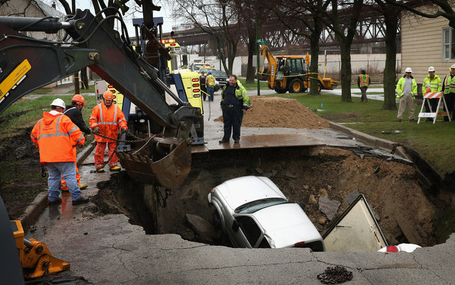 Workers prepare to pull a truck from a sinkhole that opened up on a residential street in the South Deering neighborhood on April 18, 2013 in Chicago, Illinois. The driver of the truck was hospitalized after driving into the 15-feet-deep hole while on his way to work. Two other vehicles were also swallowed by the sinkhole. (Photo by Scott Olson/AFP Photo)