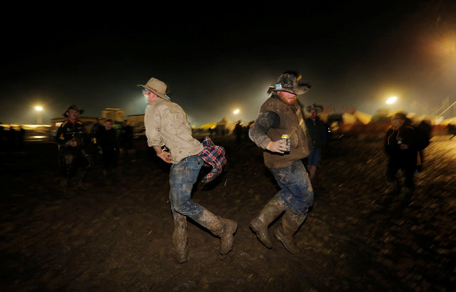 Men participate in a mud fight on the final night of the Deni Ute Muster in Deniliquin, New South Wales, Australia, October 1, 2016. (Photo by Jason Reed/Reuters)