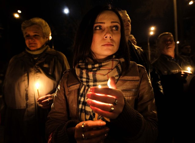 People hold candles at a service in Kiev commemorating the anniversary of the Chernobyl nuclear disaster, as Ukraine marks the 27th anniversary of the world's worst nuclear disaster, on April 26, 2013. (Photo by Sergei Chuzavkov/Associated Press)