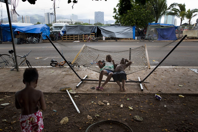 In this Tuesday, August 25, 2015 photo, two children rest on a hammock at a homeless encampment in the Kakaako district of Honolulu. (Photo by Jae C. Hong/AP Photo)