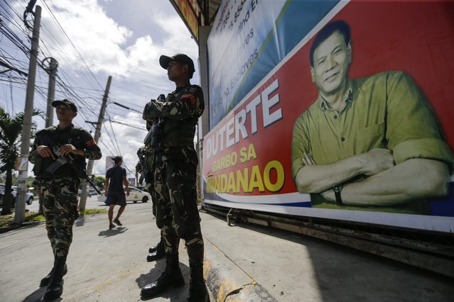 Filipino soldiers stand guard next to an election campaign poster displaying Philippine President Rodrigo Duterte (R), at a street in Davao City, southern Philippines, 16 May 2016. (Photo by Ritchie B. Tongo/EPA)