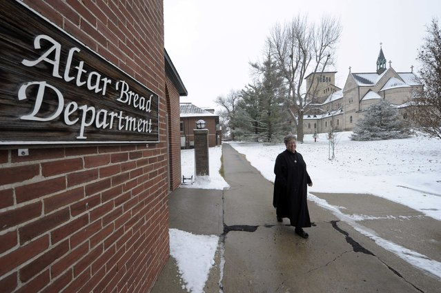 Sister Cathleen Marie Timberlake walks past the building that houses the Benedictine Sisters of Perpetual Adoration monastery's Alter Bread operation in Clyde, Missouri, December 18, 2014. (Photo by Dave Kaup/Reuters)