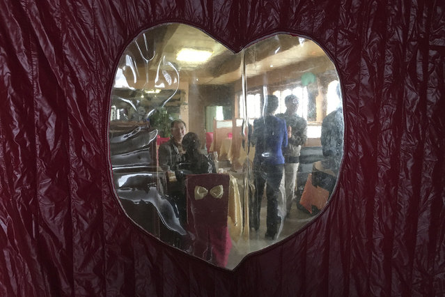 Diners are seen through a door curtain of a local restaurant during lunch hour in Pyongyang, North Korea on Sunday, October 16, 2016. (Photo by Wong Maye-E/AP Photo)