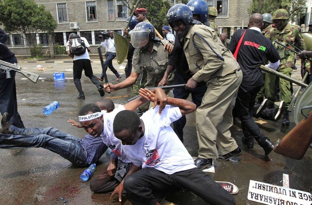Riot policemen hit protestors participating in a demonstration against lawmakers' salary demands outside the parliament buildings in the capital Nairobi, May 14, 2013. (Photo by Thomas Mukoya/Reuters)