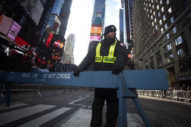 A security guard stands in Times Square as streets are closed in preparation for New Year's Eve celebrations in New York December 31, 2014. (Photo by Carlo Allegri/Reuters)