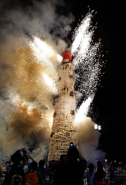 Fireworks explode on the bun tower after the Bun Scrambling contest, on May 18, 2013. The Bun Festival is a traditional event celebrating the islanders' deliverance from famine centuries ago and is meant to placate ghosts and restless spirits. (Photo by Kin Cheung/AP Photo)