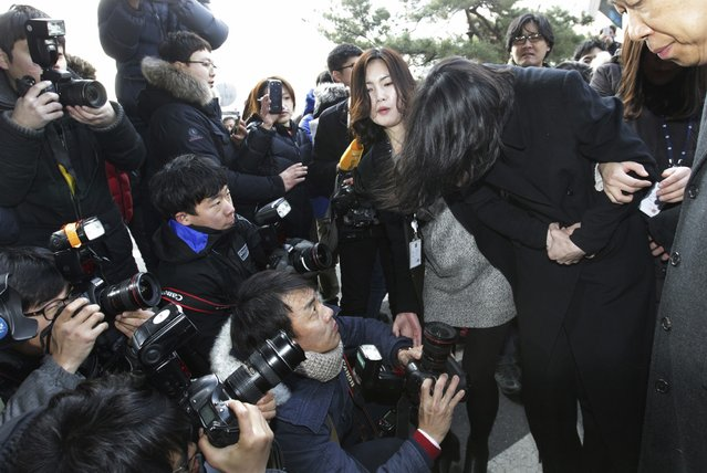 """Cho Hyun-ah, second from right, former vice president of Korean Air Lines, arrives at the Seoul Western District Prosecutors Office in Seoul, South Korea, Tuesday, December 30, 2014. A Seoul court is expected to decide Tuesday whether to issue an arrest warrant for Cho, who resigned as vice president at the airline earlier this month amid mounting public criticism over the incident that she forced a flight to return over a bag of macadamia nuts and a current executive for attempts to cover up the """"nut rage"""" case. (Photo by Ahn Young-joon/AP Photo)"""