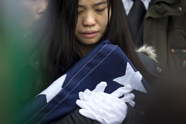 Widow Pei Xia Chen clutches the folded flag of slain New York Police Department officer Wenjian Liu as his casket departs his funeral in the Brooklyn borough of New York January 4, 2015. (Photo by Carlo Allegri/Reuters)