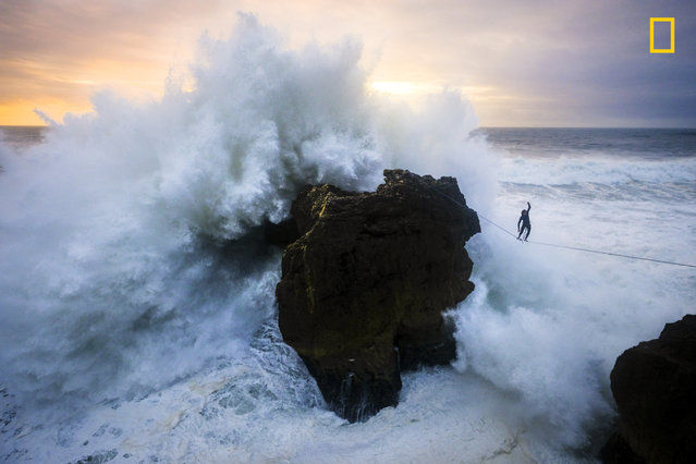 Andrey Karr from Western Riders Slacklines at sunset above big waves in Nazare, Portugal on December 27, 2017. (Photo by Aidan Williams/National Geographic Travel Photographer of the Year Contest)