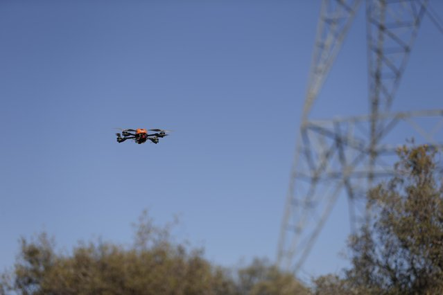In this October 16, 2014 picture, an unmanned aircraft flies near a tower carrying long-distance electric transmission lines near Boulevard, Calif. San Diego Gas and Electric thinks that drones might be a cheaper, faster way to inspect its power lines in remote areas. (Photo by Gregory Bull/AP Photo)