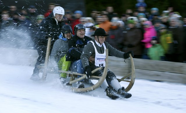 Four men ride their wooden sledge during a traditional Bavarian horn sledge race in the Alpine resort of Garmisch-Partenkirchen January 6, 2015. The sledge race is an annual event to remember the traditional way of bringing hay, straw and wood down from the Alpine mountains to the valley. (Photo by Michaela Rehle/Reuters)