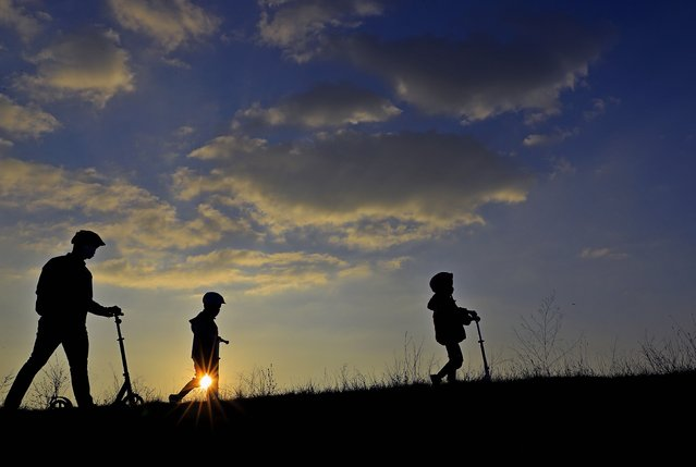 A father and his sons, as seen against the sun, walk at sunset on the side dam of Vacaresti wild park, in Bucharest, Romania, 15 November 2020. (Photo by Robert Ghement/EPA/EFE)