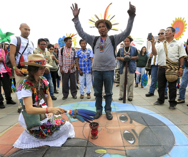 A Colombian Barzano man and a woman take part in a symbolic ritual before a march ahead of the 2015 Paris Climate Change Conference (COP21), in Bogota, Colombia November 29, 2015. (Photo by Jose Miguel Gomez/Reuters)
