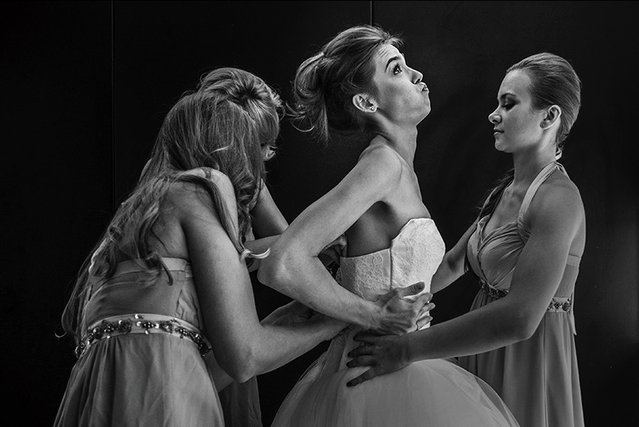 The Bride getting into her dress wiht her Bridesmaids. Bristol, UK. (Photo by Rich Howman/Caters News)
