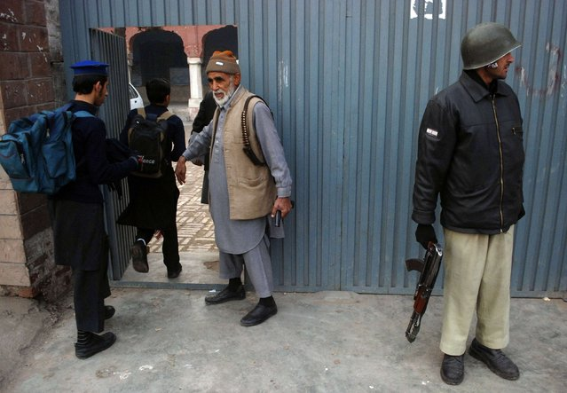 Students walk past an entrance as a policeman (R) and a staff member stand guard outside a school after it reopened in Peshawar January 12, 2015. (Photo by Khuram Parvez/Reuters)