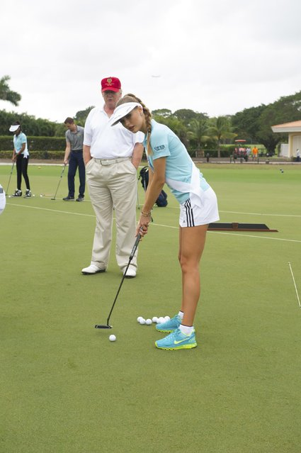 Donald Trump gives some putting tips to Diana Harkusha, Miss Ukraine 2014 at the 63rd annual Miss Universe Pageant in Miami, Florida in this January 12, 2015 handout photo provided by Miss Universe Organization. (Photo by Reuters/Miss Universe Organization)
