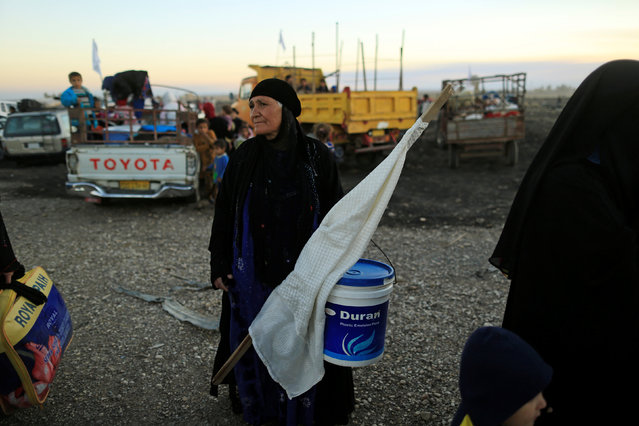 A woman who had just fled Kokjali near Mosul carries a white flag as she arrives with her family at a Peshmerga checkpoint east of Mosul, Iraq November 3, 2016. (Photo by Zohra Bensemra/Reuters)