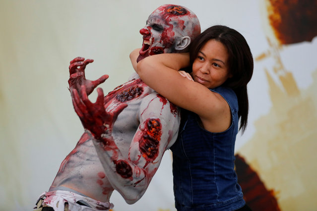 An attendee poses for a picture with a zombie at E3, the world's largest video game industry convention in Los Angeles, California on June 12, 2018. (Photo by Mike Blake/Reuters)