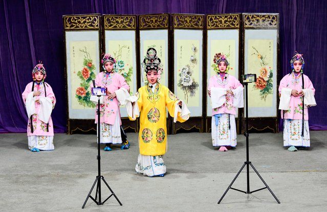 A live stream is broadcast on the mobile phones as children perform Peking Opera to welcome the upcoming Chinese New Year, the Year of the Ox, on February 1, 2021 in Hohhot, Inner Mongolia Autonomous Region of China. (Photo by Wang Zheng/VCG via Getty Images)