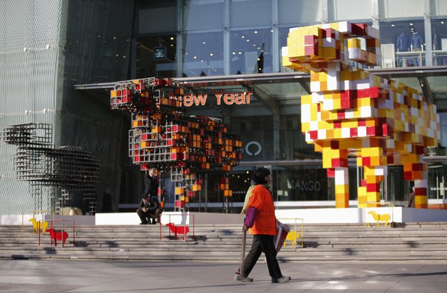 A cleaner walks past art installations celebrating the Chinese New Year of the Goat, at a shopping mall in Beijing January 21, 2015. China's sound economic fundamentals have not changed and the government will put more focus on structural reforms this year, Premier Li Keqiang was quoted on Wednesday as saying. (Photo by Kim Kyung-Hoon/Reuters)