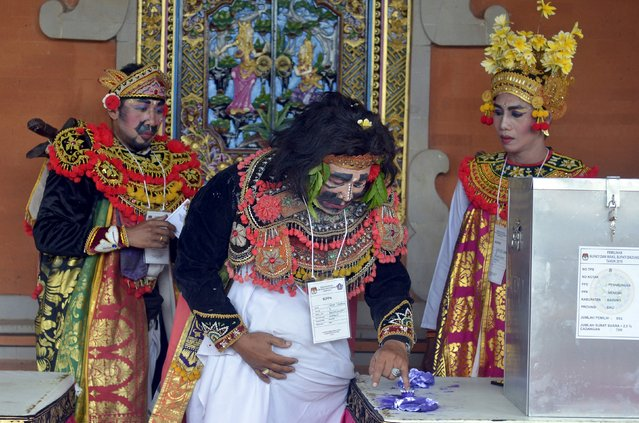 Polling station officials dressed as traditional Balinese performers vote in Badung regency on the Indonesian island of  Bali December 9, 2015 in this photo taken by Antara Foto. Around 100 million Indonesians were expected to go to the polls on Wednesday in many parts of the country to elect heads of local government. (Photo by Wira Suryantala/Reuters/Antara Foto)