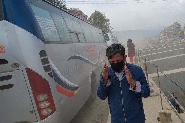 As the government ploughs on with its controversial road expansion scheme, commuting in Nepal's capital can take up to four hours – while many joke that the dust mask has become part of the national dress. (Photo by Pete Pattisson/The Guardian)