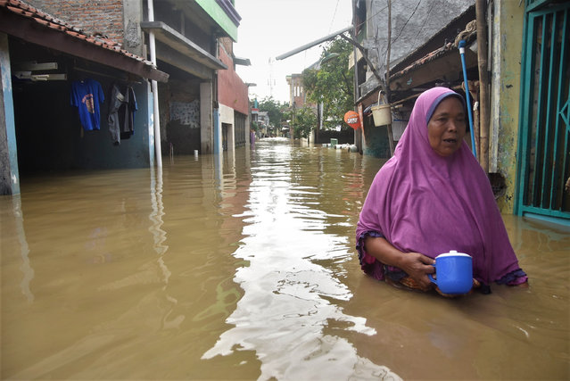A woman makes her way along a flooded street in Bekasi, on the outskirts of Jakarta on February 8, 2021. (Photo by Rezas/AFP Photo)