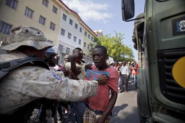 A protester is detained by police during a demonstration to demand the resignation of President Michel Martelly, in Port-au-Prince, Haiti. Saturday, January 17, 2015. The protest was the latest in a series of demonstrations demanding Martelly leave office before his term expires next year. (Photo by Dieu Nalio Chery/AP Photo)
