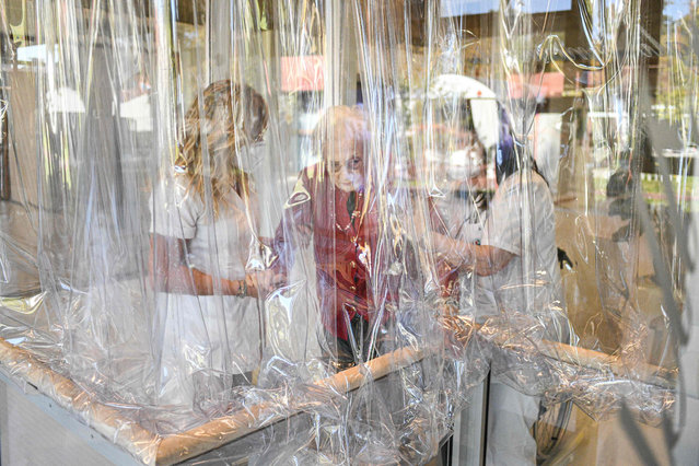 """A resident (C) of the Domenico Sartor nursing home is helped by nurses before talking to a relative through a plastic screen on November 11, 2020 in Castelfranco Veneto, near Venice, in a so-called """"Hug Room"""" amid the new coronavirus pandemic. The Hug Room allows guests and their families to embrace each other, while remaining separate and protected from the contagious disease, still guaranteeing physical contact for mental and emotional wellbeing. (Photo by Piero Cruciatti/AFP Photo)"""