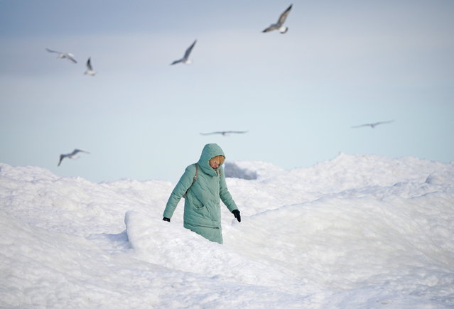 A woman walks along the shore of the partially frozen Baltic sea in Zelenogradsk, Kaliningrad Region, Russia on February 12, 2021. (Photo by Vitaly Nevar/Reuters)