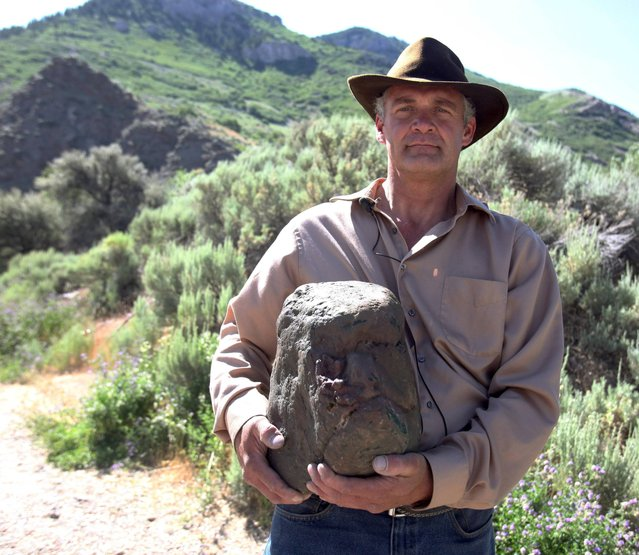 """Todd May holds what he believes to be a fossilized head of a bigfoot Tuesday, June 18, 2013 in Ogden, Utah. He says he has also seen a couple of the non-fossilized, live skulls – attached to their monstrous, hairy bodies – in recent years. """"I've been tracking and watching for Bigfoot"""", May said. """"I'm very curious, interested in that, and wanted to get footage on it 'cause I've ran across him a couple of times"""". (Photo by Nick Short/AP Photo/Standard-Examiner)"""
