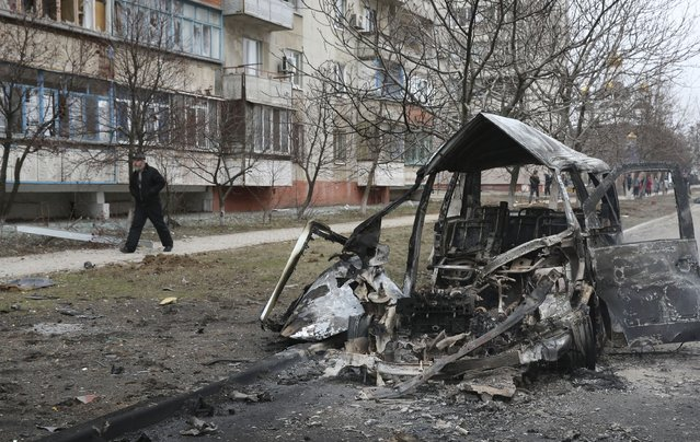 A man walks past a burnt-out vehicle after a shelling by pro-Russian rebels of a residential sector in Mariupol, eastern Ukraine, January 24, 2015. Fifteen people were killed in shelling in the east Ukrainian port city of Mariupol on Saturday, Ukraine's interior ministry said, an attack Kiev blamed on separatist rebels and the Russian military. (Photo by Reuters/Stringer)