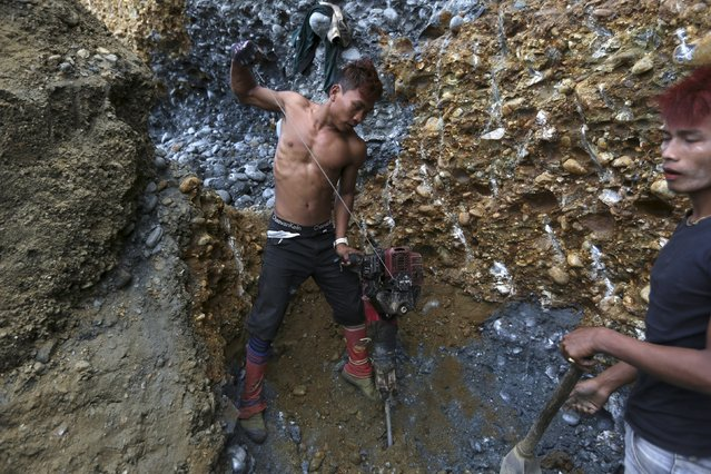 Miners search for jade stones at a mine dump at a Hpakant jade mine in Kachin state, Myanmar November 27, 2015. (Photo by Soe Zeya Tun/Reuters)