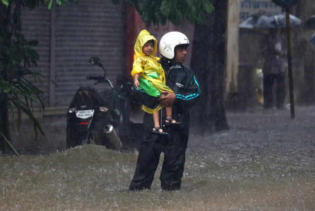 A man holds a child at a waterlogged road during heavy rains in Mumbai, July 9, 2018. (Photo by Francis Mascarenhas/Reuters)