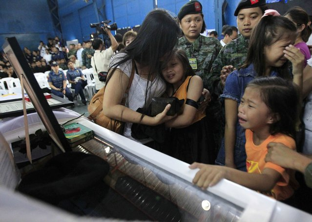Children cry in front of the casket for their father, one of the slain members of the Special Action Force (SAF) who were killed in Sunday's clash with Muslim rebels, during a service inside a police headquarters in Taguig city, south of Manila January 30, 2015. (Photo by Romeo Ranoco/Reuters)