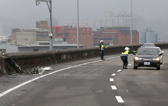 Policemen control traffic next to the wreckage of a TransAsia Airways plane which hit a motorway before crash landing in a river, in New Taipei City, February 4, 2015. (Photo by Reuters/Stringer)