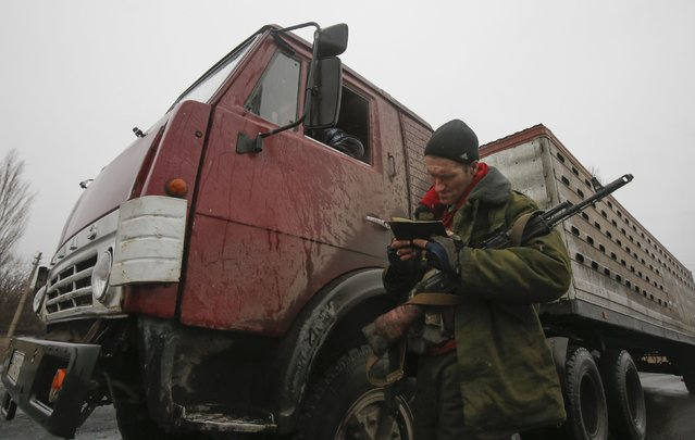 A pro-Russian separatist checks a driver's documents in Zhdanivka town, northeast from Donetsk, February 2, 2015. (Photo by Maxim Shemetov/Reuters)
