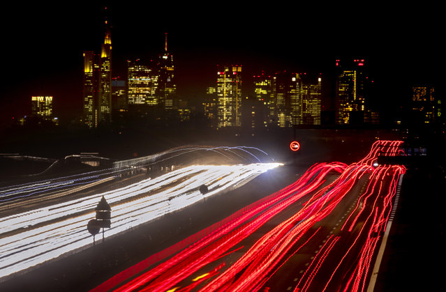 A long time exposure photo shows cars and trucks driving on a highway near Frankfurt, Germany, Tuesday, November 17, 2020. In background the buildings of the banking district. (Photo by Michael Probst/AP Photo)