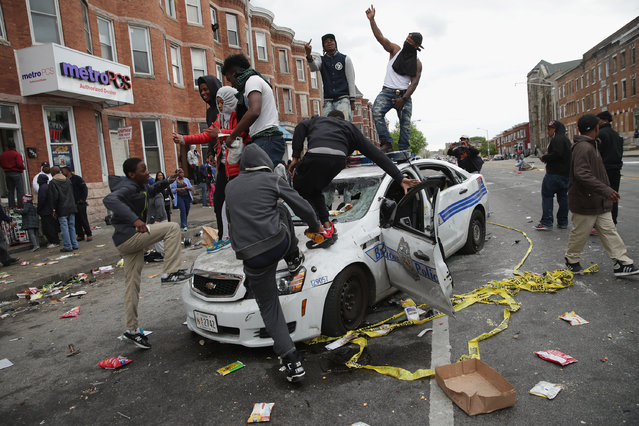 Demonstrators climb on a destroyed Baltimore Police car in the street near the corner of Pennsylvania and North avenues during violent protests following the funeral of Freddie Gray April 27, 2015 in Baltimore, Maryland. Gray, 25, who was arrested for possessing a switch blade knife April 12 outside the Gilmor Homes housing project on Baltimore's west side. According to his attorney, Gray died a week later in the hospital from a severe spinal cord injury he received while in police custody. (Photo by Chip Somodevilla/Getty Images)