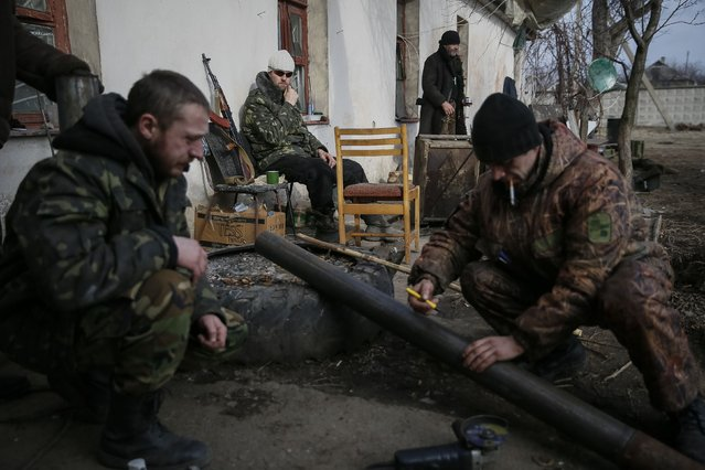 A Ukrainian serviceman rests as his comrades make a pipe for a wood stove near Debaltseve, eastern Ukraine, February 8, 2015. (Photo by Gleb Garanich/Reuters)