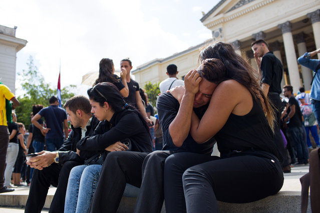 From left to right Alejandro Peraza Peña, 21,  Yaxelys Pereda Orraca, 18, Noxcy Palacio, 21, and Diana Legar, 23, mourn the death of Fidel after a student rally in his honor at the University of Havana, Cuba on November 26, 2016. Palacio says he owes his mother's life to Fidel because two years ago she was diagnosed with terminal cancer, through Cuba's healthcare system, she received free treatment and recovered. He also remembers seeing Fidel speak in person at his school's inauguration in 2002, only 7 years old then, he says his presence was undeniable and he has chills hearing his leader's voice live. (Photo by Lisette Poole/The Washington Post)